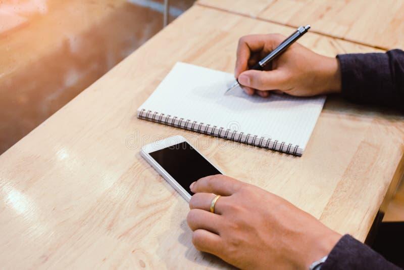 Uomo d'affari nella penna di tenuta nera delle mani della camicia che indica al documento di affari sullo scrittorio fotografia stock