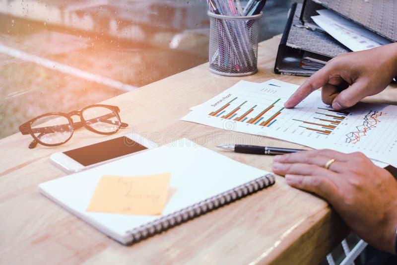 Uomo d'affari nella penna di tenuta nera delle mani della camicia che indica al documento di affari sullo scrittorio immagini stock