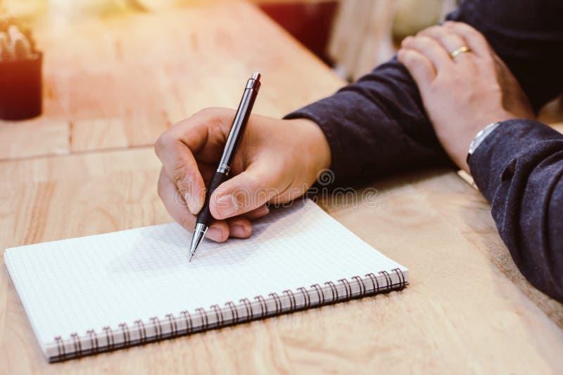 Uomo d'affari nella penna di tenuta nera delle mani della camicia che indica al documento di affari sullo scrittorio fotografie stock