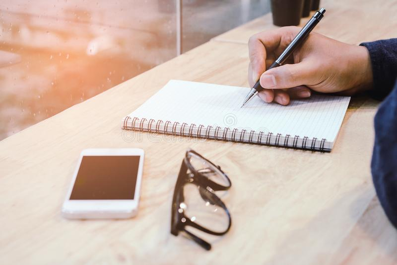 Uomo d'affari nella penna di tenuta nera delle mani della camicia che indica al documento di affari sullo scrittorio fotografie stock libere da diritti