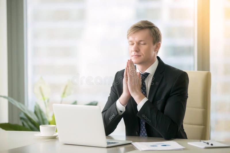 Uomo d'affari nella posa di yoga alla scrivania fotografie stock