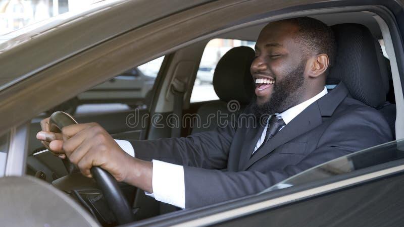 Uomo d'affari nero allegro che si siede in automobile di lusso, prova su strada, trasporto fotografia stock