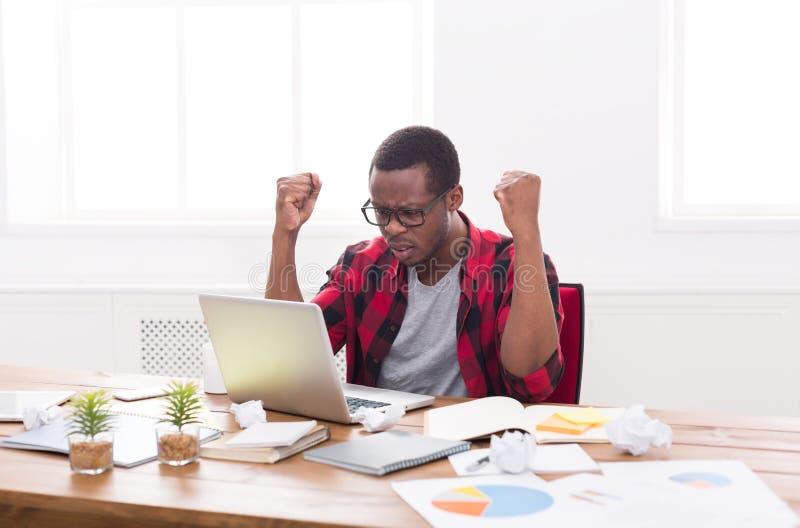 Uomo d'affari nero arrabbiato in ufficio, lavoro con il computer portatile fotografia stock