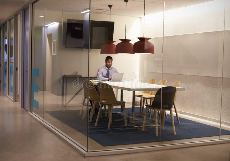 Uomo d'affari nero che lavora nel cubicolo ad un affare corporativo fotografia stock libera da diritti