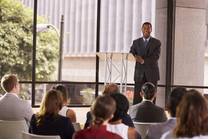 Uomo d'affari nero che presenta seminario che sorride al pubblico immagine stock