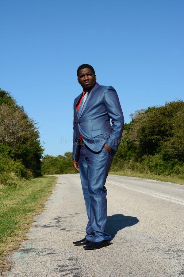 Uomo d'affari nero che sta sulla strada immagini stock