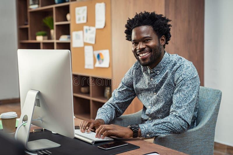 Uomo d'affari nero creativo che lavora al computer fotografia stock