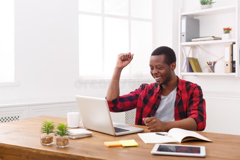 Uomo d'affari nero felice in ufficio moderno, lavoro con il computer portatile immagini stock libere da diritti