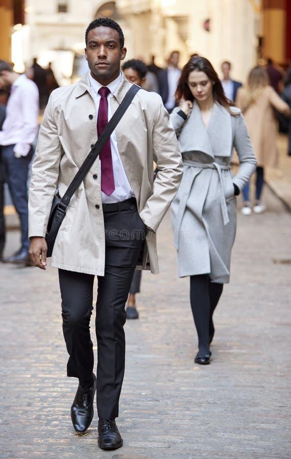 Uomo d'affari nero millenario che cammina in una via della città che guarda alla macchina fotografica, integrale fotografie stock libere da diritti