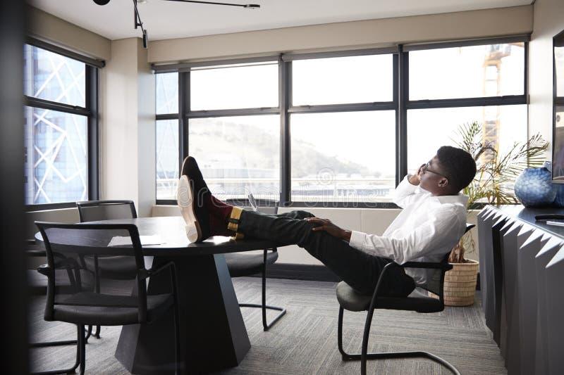 Uomo d'affari nero millenario che parla sul telefono che si siede con i piedi su sullo scrittorio in una sala riunioni immagine stock