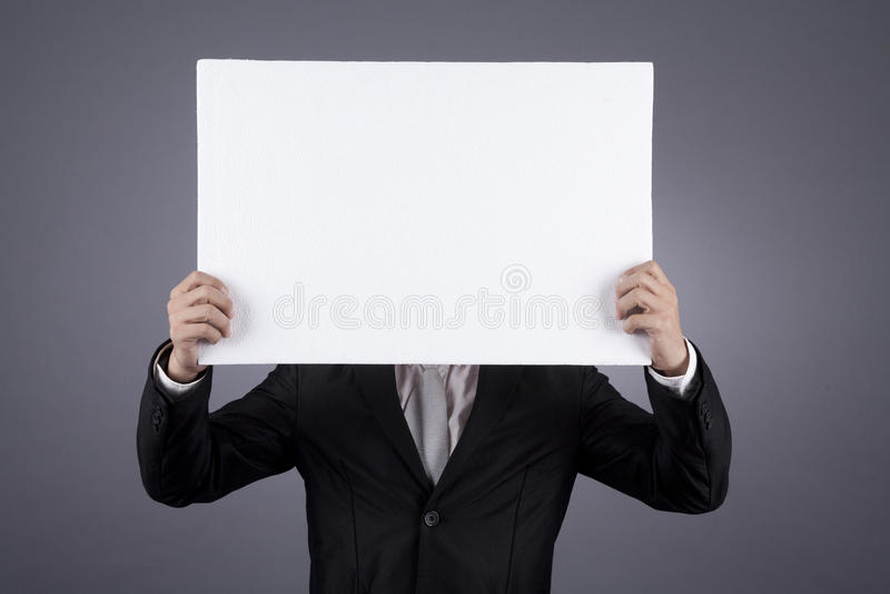 Uomo d'affari non riconosciuto che tiene un segno in bianco fotografie stock libere da diritti