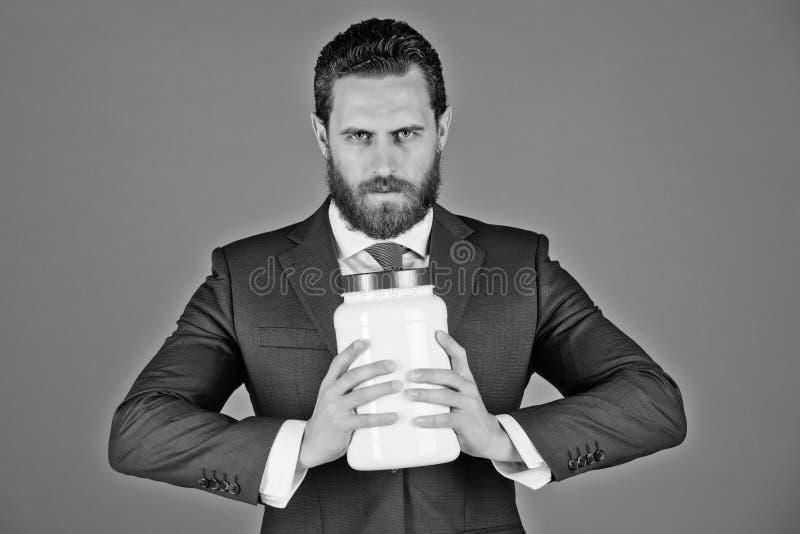 Uomo d'affari o uomo barbuto con il barattolo di plastica su fondo blu fotografie stock