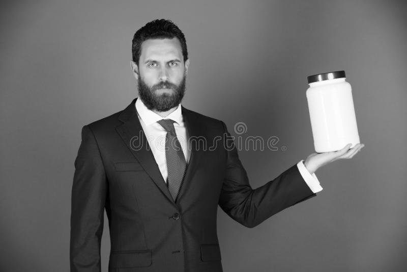 Uomo d'affari o uomo barbuto con il barattolo di plastica su fondo blu fotografie stock libere da diritti