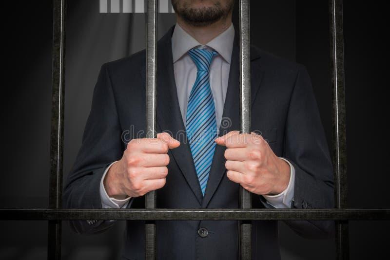 Uomo d'affari o politico dietro le barre in cella di prigione fotografia stock