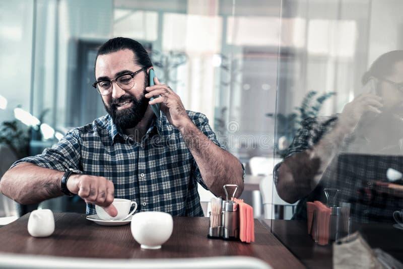 Uomo d'affari occupato che chiama il suo collega mentre organizzando riunione immagini stock libere da diritti