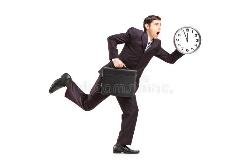 Uomo d'affari occupato che funziona con l'orologio e la cartella di parete immagine stock libera da diritti