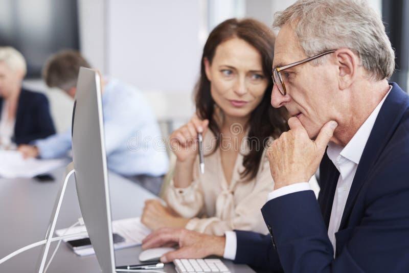 Uomo d'affari occupato che per mezzo di un computer nel corso della riunione d'affari fotografia stock libera da diritti