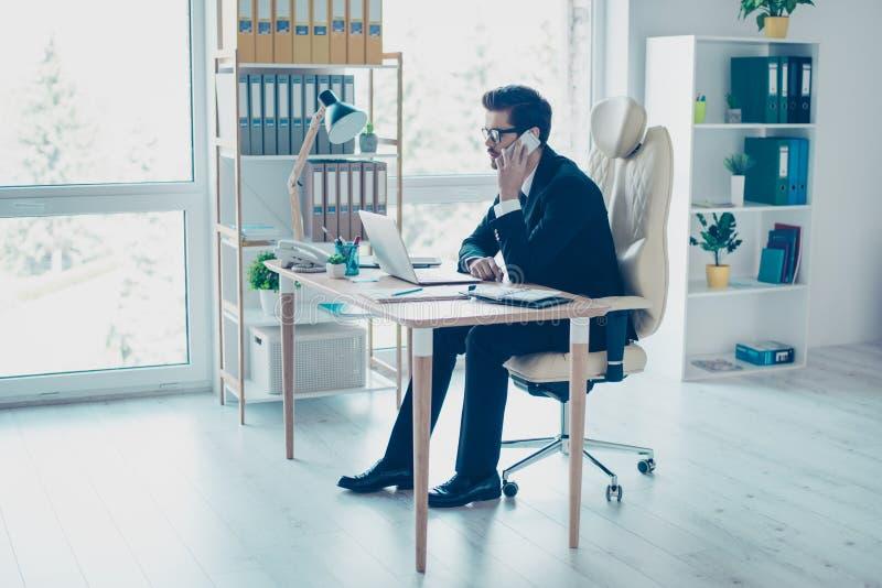 Uomo d'affari occupato di occupato che si siede all'ufficio e che fa una chiamata alla h fotografie stock libere da diritti