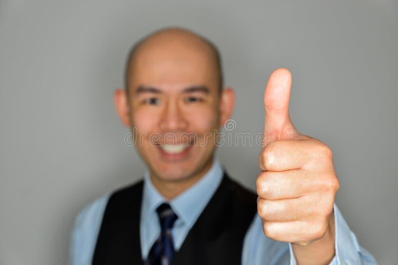 Uomo d'affari Offering Thumbs Up e sorriso immagine stock