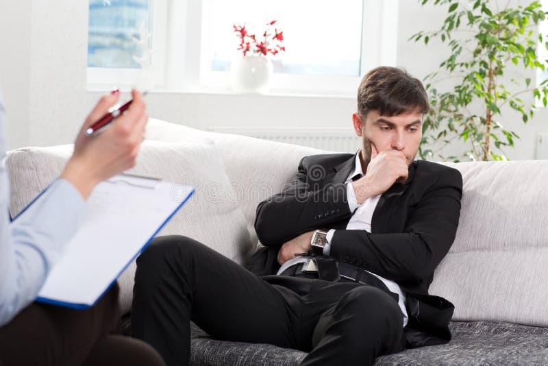 Uomo d'affari opprimente che parla con lo psicologo fotografia stock