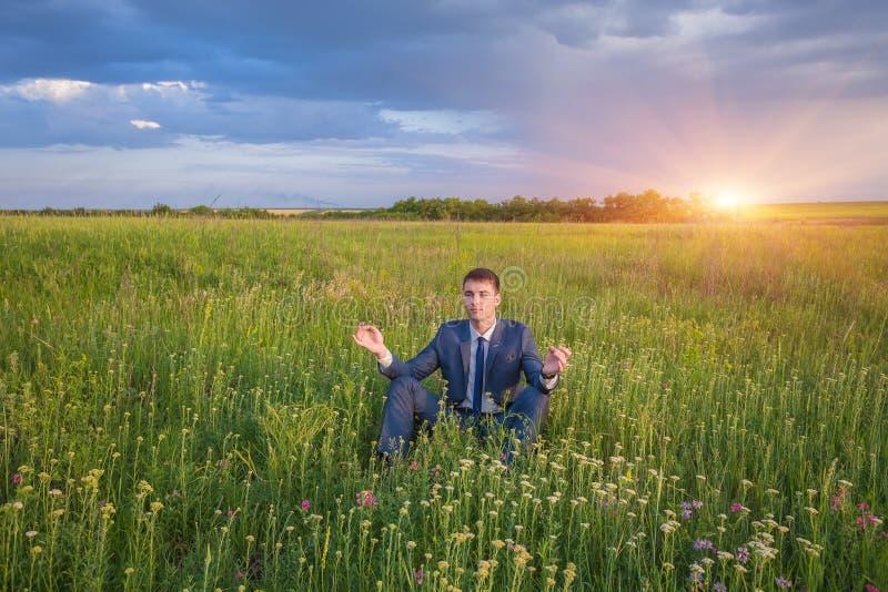 Uomo d'affari pacifico che si siede nella posa del loto fotografie stock libere da diritti