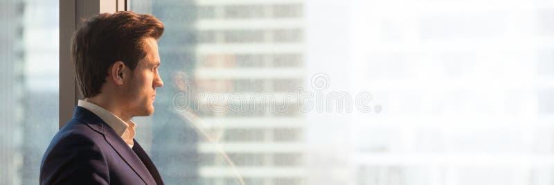 Uomo d'affari panoramico di immagine in vestito che guarda attraverso la finestra dell'ufficio fotografia stock libera da diritti