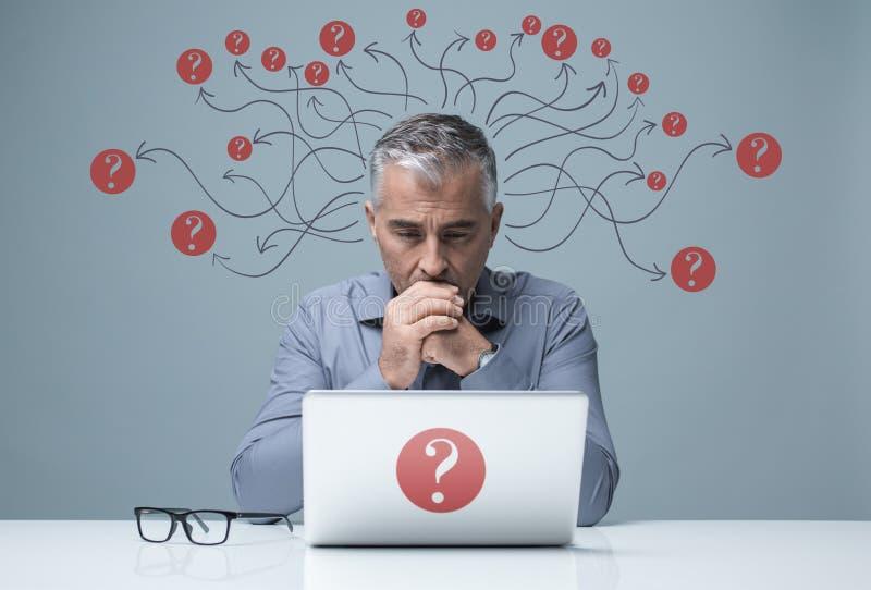 Uomo d'affari pensieroso che lavora con un computer portatile immagini stock