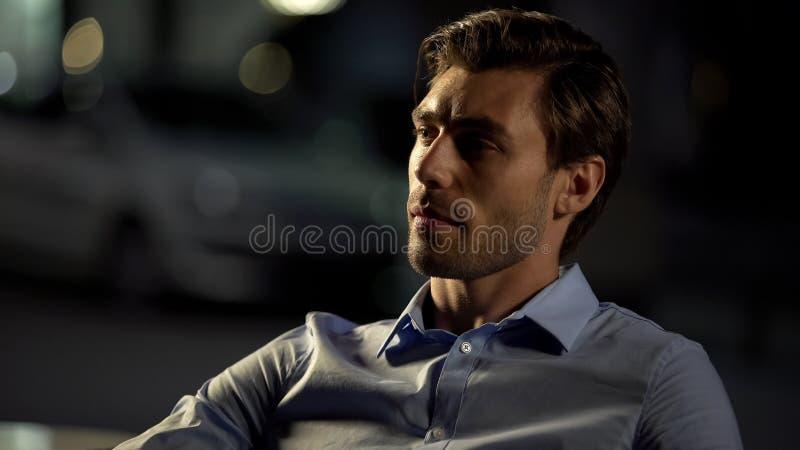 Uomo d'affari pensieroso che si siede in caffè, stanco dopo la giornata campale, bevande aspettanti fotografia stock libera da diritti