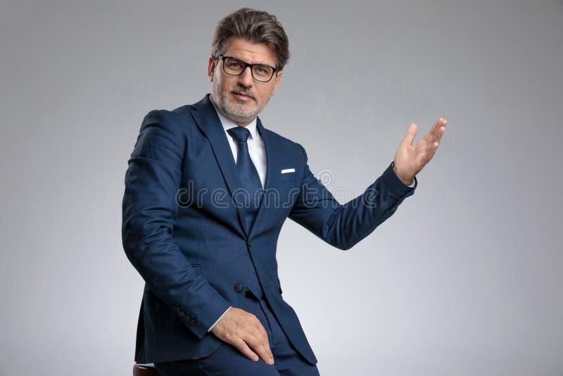 Uomo d'affari positivo che gesturing un saluto mentre sedendosi fotografie stock