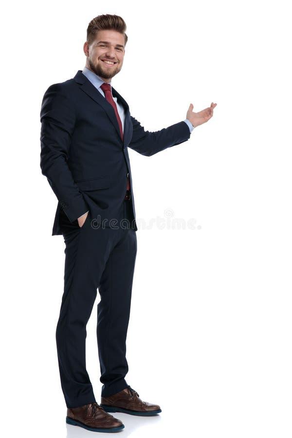 Uomo d'affari positivo che presenta e che tiene la sua mano in sua tasca fotografia stock