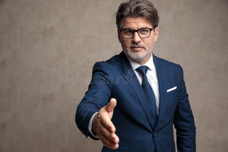 Uomo d'affari positivo che raggiunge per una stretta di mano immagini stock