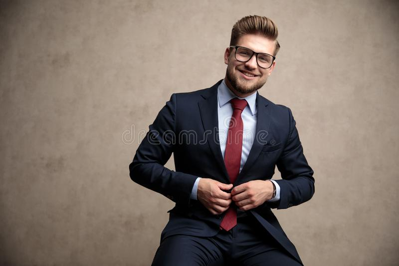 Uomo d'affari positivo che regola il suoi rivestimento e risata fotografia stock