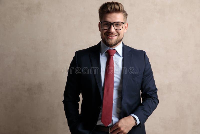 Uomo d'affari positivo che ride con la sua mano in sua tasca fotografia stock libera da diritti