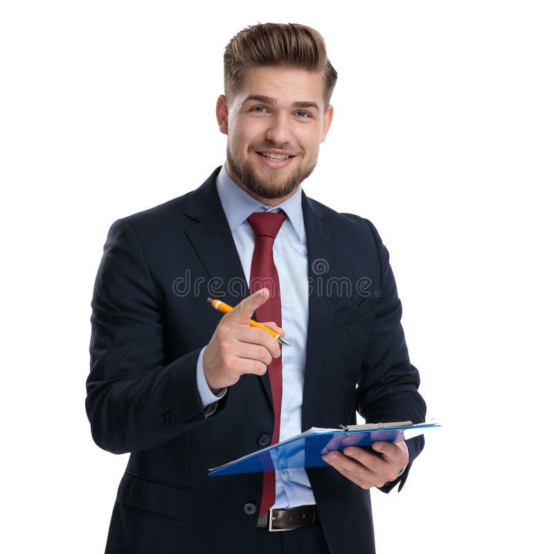 Uomo d'affari positivo che spiega e che tiene la sua lavagna per appunti fotografia stock
