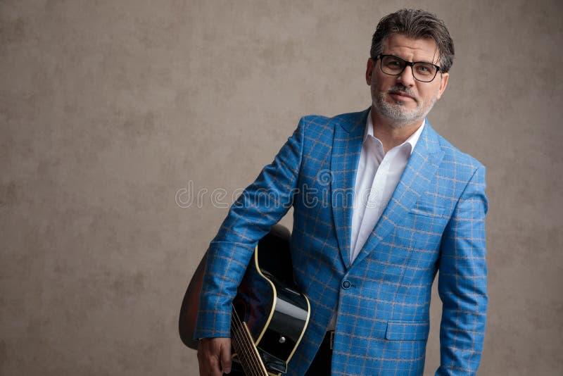 Uomo d'affari positivo che tiene la suoi chitarra e sorridere immagine stock libera da diritti