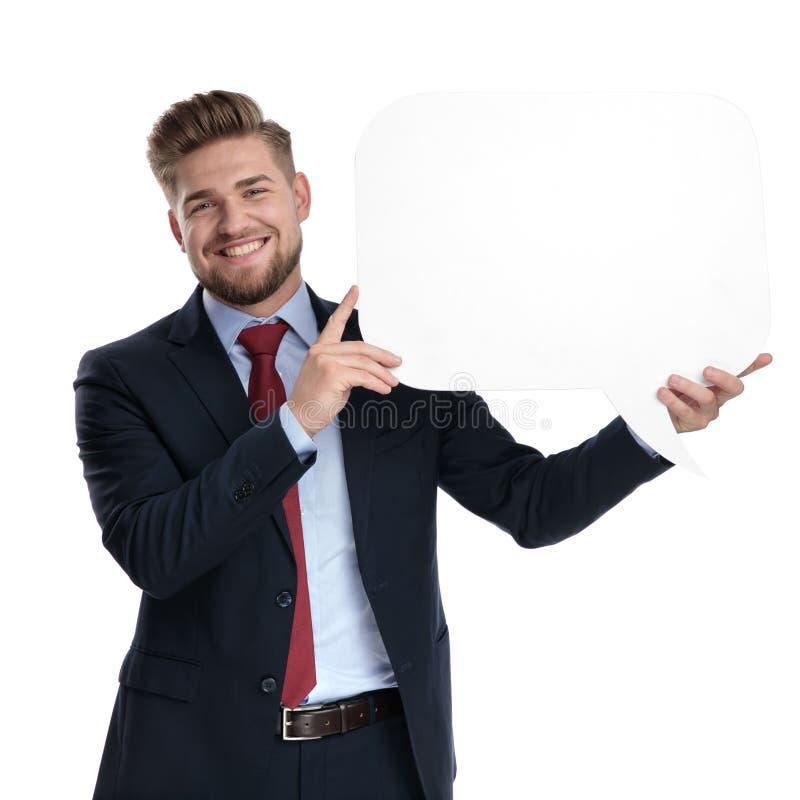 Uomo d'affari positivo che tiene un fumetto e una risata in bianco fotografia stock