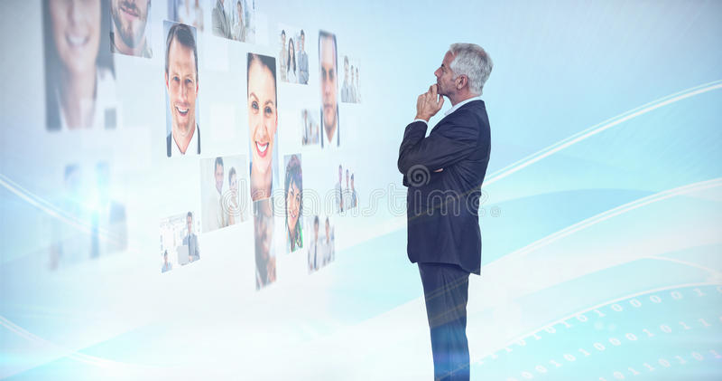 Uomo d'affari premuroso che esamina una parete coperta dalle immagini di profilo fotografie stock libere da diritti