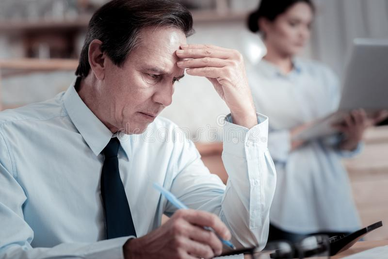 Uomo d'affari preoccupato che aggrotta le sopracciglia e che tocca la sua fronte immagini stock