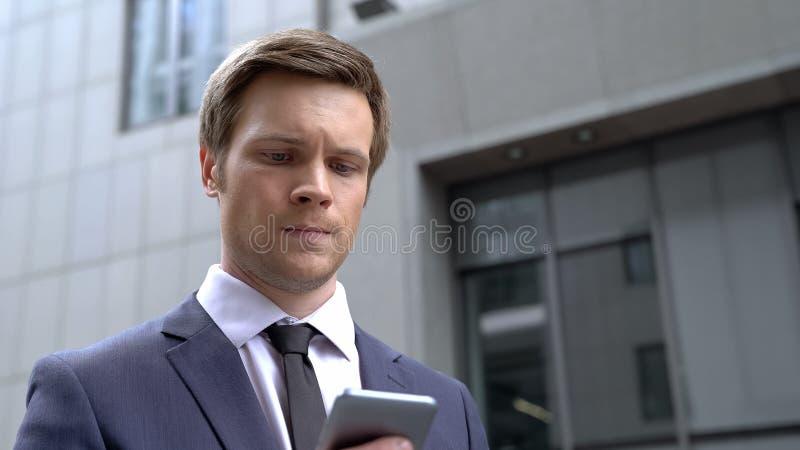 Uomo d'affari preoccupato che riceve cattive notizie sullo smartphone, situazione disperata, venire a mancare immagini stock