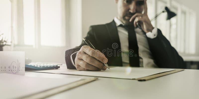 Uomo d'affari preoccupato che si siede al suo funzionamento dello scrittorio sulla tassa e sul lavoro di ufficio finanziario immagini stock