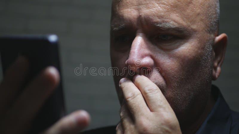 Uomo d'affari preoccupato Image nell'oscurità facendo uso della comunicazione senza fili di Smartphone immagine stock libera da diritti