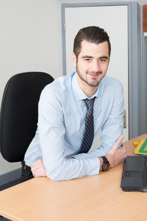 Uomo d'affari professionale che posa nel suo ufficio e che sorride alla macchina fotografica che si siede allo scrittorio ed al l fotografie stock