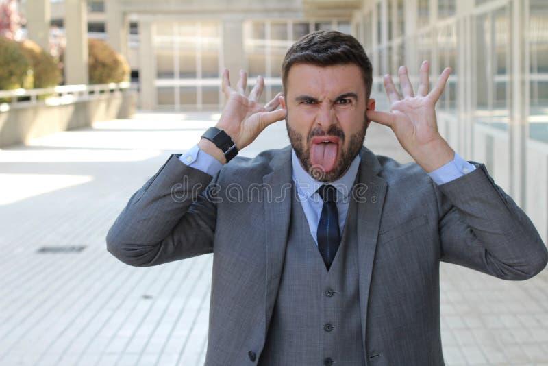 Uomo d'affari puerile che fa un gesto osceno immagini stock libere da diritti