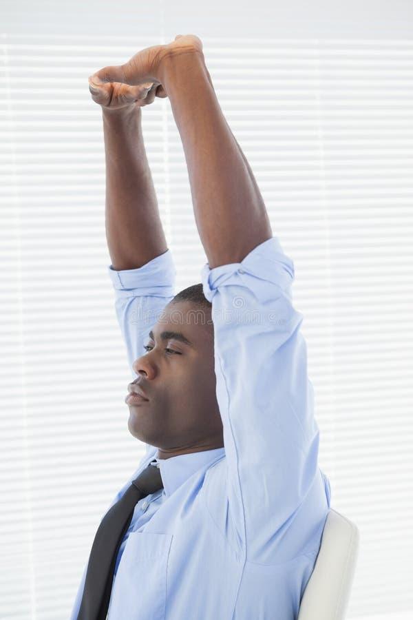 Uomo d'affari rilassato che allunga nella sua sedia fotografie stock libere da diritti