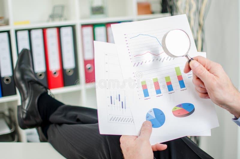 Uomo d'affari rilassato che analizza un grafico finanziario fotografia stock libera da diritti