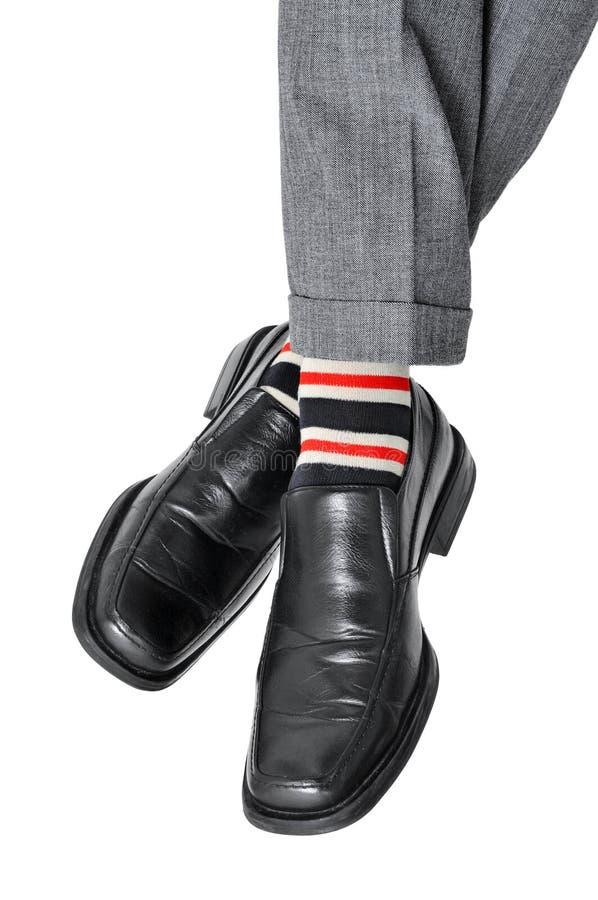 Uomo d'affari rilassato che attraversa i suoi piedi immagine stock