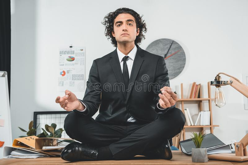 uomo d'affari rilassato che medita mentre sedendosi sulla tavola nella posa del loto immagine stock