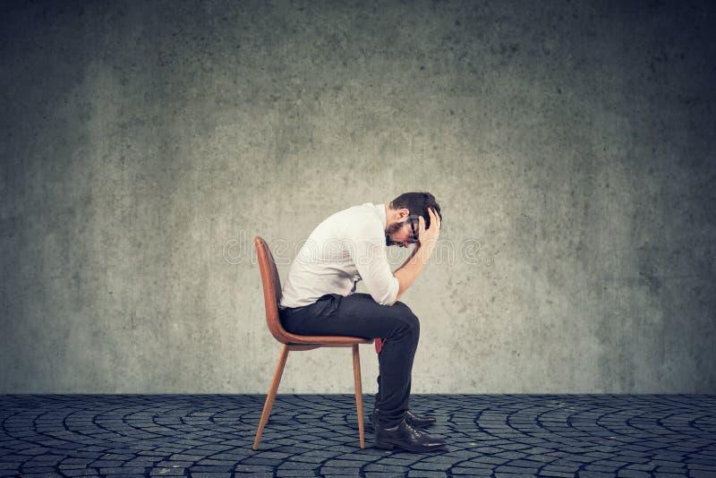 Uomo d'affari rotto triste che si siede in un ufficio vuoto fotografie stock libere da diritti