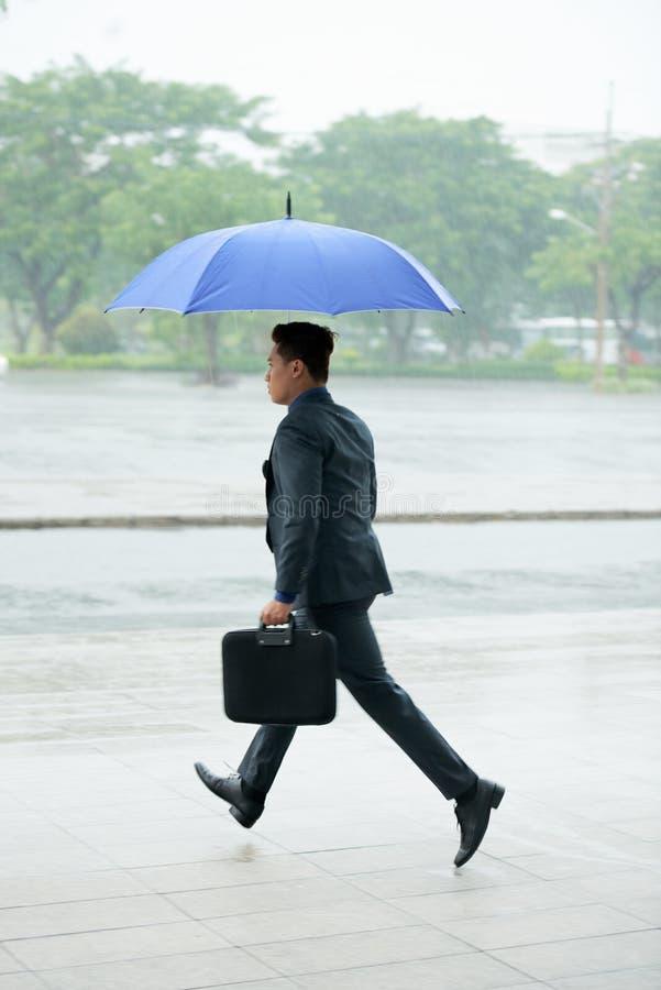 Uomo d'affari Running con l'ombrello fotografia stock