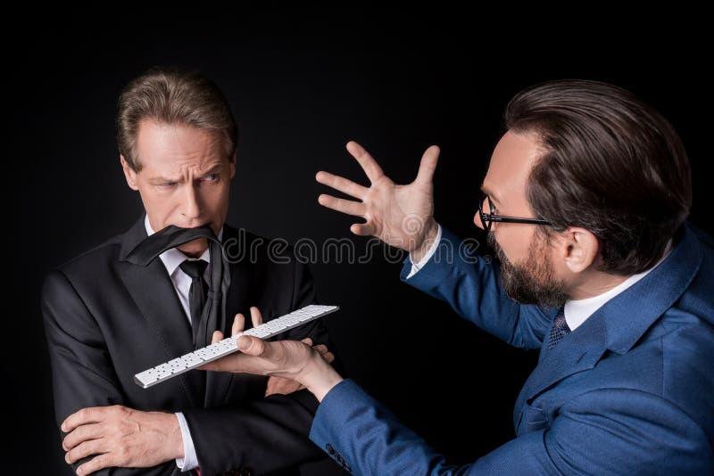 Uomo d'affari scettico con la cravatta in bocca che esamina la tastiera emozionale della tenuta del collega e che litiga fotografia stock libera da diritti